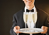 A waiter holding a tray of champagne glasses