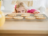 Girl (4-5) reaching for cookies