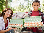 USA, New York, Flanders, Mother and son (8-9) selling fresh eggs