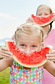 Girls (6-7, 8-9) eating watermelon