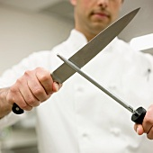 Chef sharpening knife in kitchen