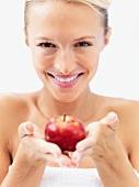 Blond woman holding an apple
