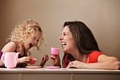 Mother and daughter drinking tea from doll's tea set