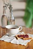 Teetasse mit Teebeutel und angebissenes Marmeladenbrot