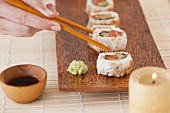 Woman holding sushi by chopsticks