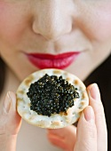 Young woman eating caviar snack, close-up of lips