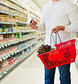 Man shopping, holding basket and can