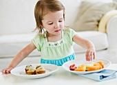 Girl (2-3) choosing between fruit salad and muffins