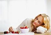 Nachdenkliche junge Frau beim Auswählen der Erdbeeren
