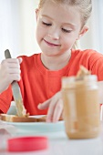 Mädchen bestreicht Brotscheibe mit Erdnussbutter