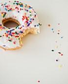 Ein angebissener Donut mit Zuckerguss & bunten Streuseln