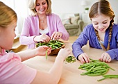USA, Jersey City, New Jersey, mother and daughters (8-11) husking vegetables