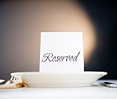 Reserved sign on place setting, studio shot