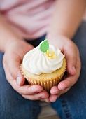 Close up of girl's (8-9) hands holding cupcake
