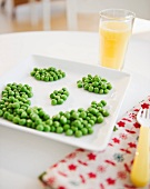 Close up of smiley on plate made of green peas