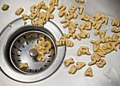 Buchstabennudeln im Ausgussbecken einer Spüle