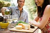 Junges Paar mit Brotzeit & Wein im Freien