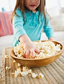 Small girl (4-5 years) eating popcorn