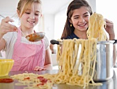 Two girls cooking pasta