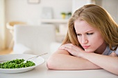 Woman leaning on table looking on green peas