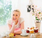Smiling young woman in apron leaning on table with cakes