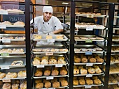 Baker standing behind trays of baked goods