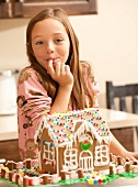 Portrait of girl (6-7) licking finger by gingerbread house