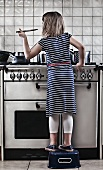 Girl (8-9) cooking in kitchen