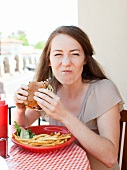 Portrait of young woman having burger