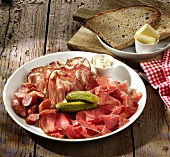 Sausage and ham platter with pickled gherkins, bread and butter