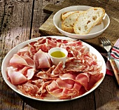 Sausage and ham platter with olive oil and white bread