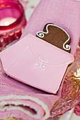 Handbag cookie on a pink cloth napkin in front of a tea light