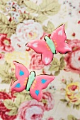 Two pink 'butterfly' cookies on a floral background