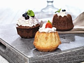 Three small Bundt cakes with cream and berries