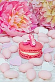 Pink macron decorated with home made 'pumps', surrounded by sugared almonds, sugar candies and peonies