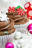 Chocolate cupcakes decorated with sugar flowers and snow flakes for Christmas