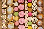 Reihen von Cupcakes, Scones, Macarons, Biskuitrolle und Stücke von Mini Battenburg Cake