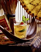 Whiskey sour with lime wedges and ice cubes