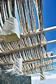 Pergola mit geflochtenen Seilsträngen Abdeckung und aufgehängten Leuchten mit weißem Stoffschirm
