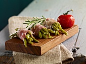 Green beans wrapped in bacon with rosemary on a small wooden board