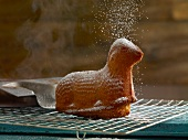 Easter lamb (cake) on cooling rack being sprinkled with powdered sugar
