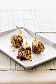 Chocolate covered pears with chopped nuts