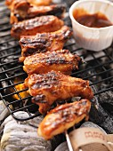 Barbecued chicken wings and barbecue sauce on the barbecue