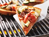 A slice of pizza, cooked on the barbecue, on a spatula