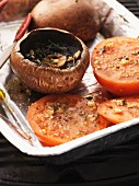Barbecued portobello mushrooms and tomatoes in an aluminium tray