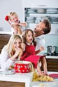 Familie spielt mit Spaghetti auf Arbeitsplatte in der Küche