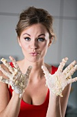 Germany, Young woman hands covered with batter