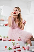 Germany, Young woman biting strawberry, glasses with strawberry yogurt