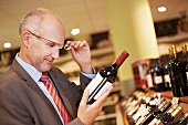 Germany, Cologne, Mature man inspecting wine bottle in supermarket