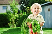 Germany, Bavaria, Boy holding radish and carrots, smiling